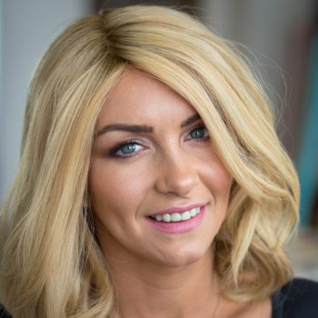 Smiling Alopecia Areata Client with her blonde mid length Enhancer system