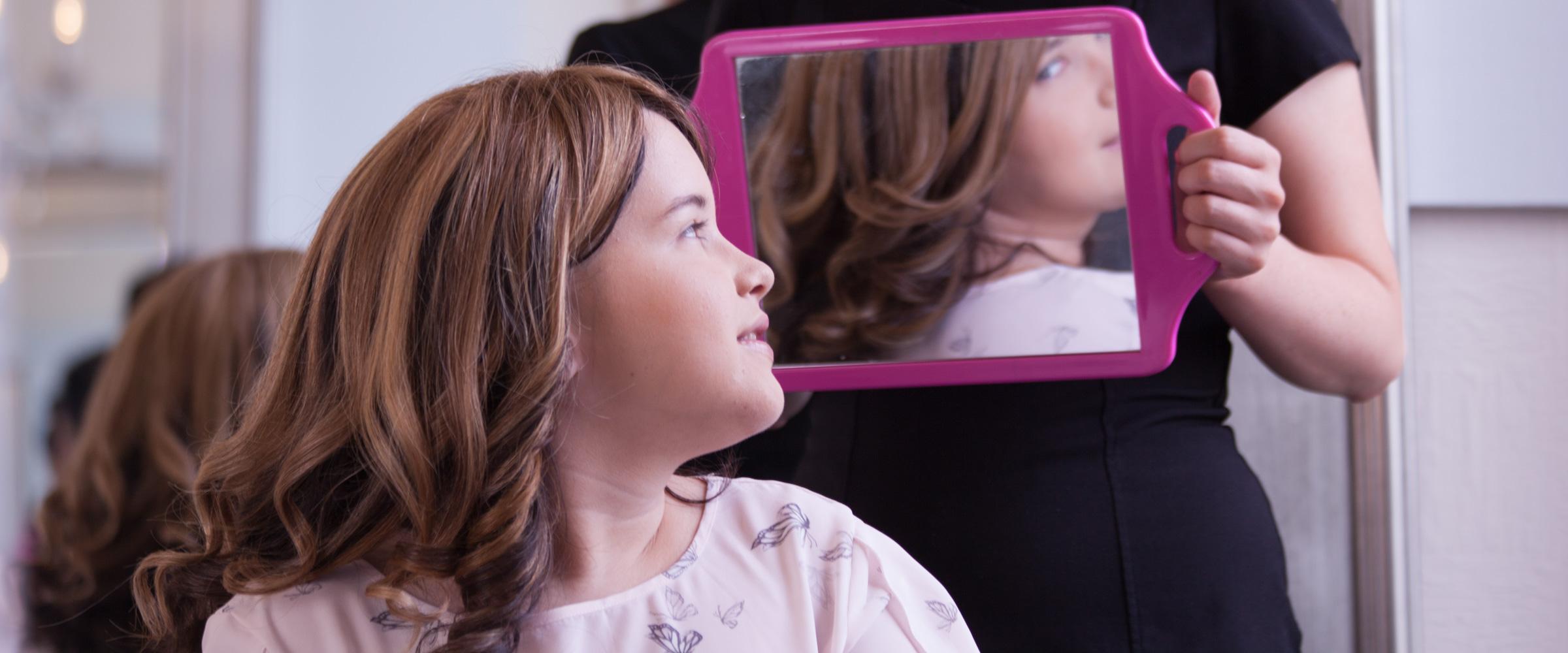 Teenage girl admires hair in mirror