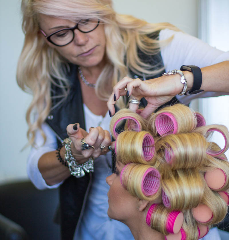 Female Stylist putting rollers in Alopecia Areata client's Enhancer System