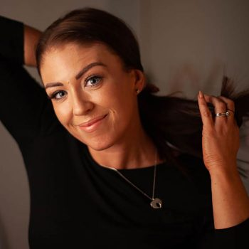 Louise twists her long dark brown enhancer system naturally through her fingers